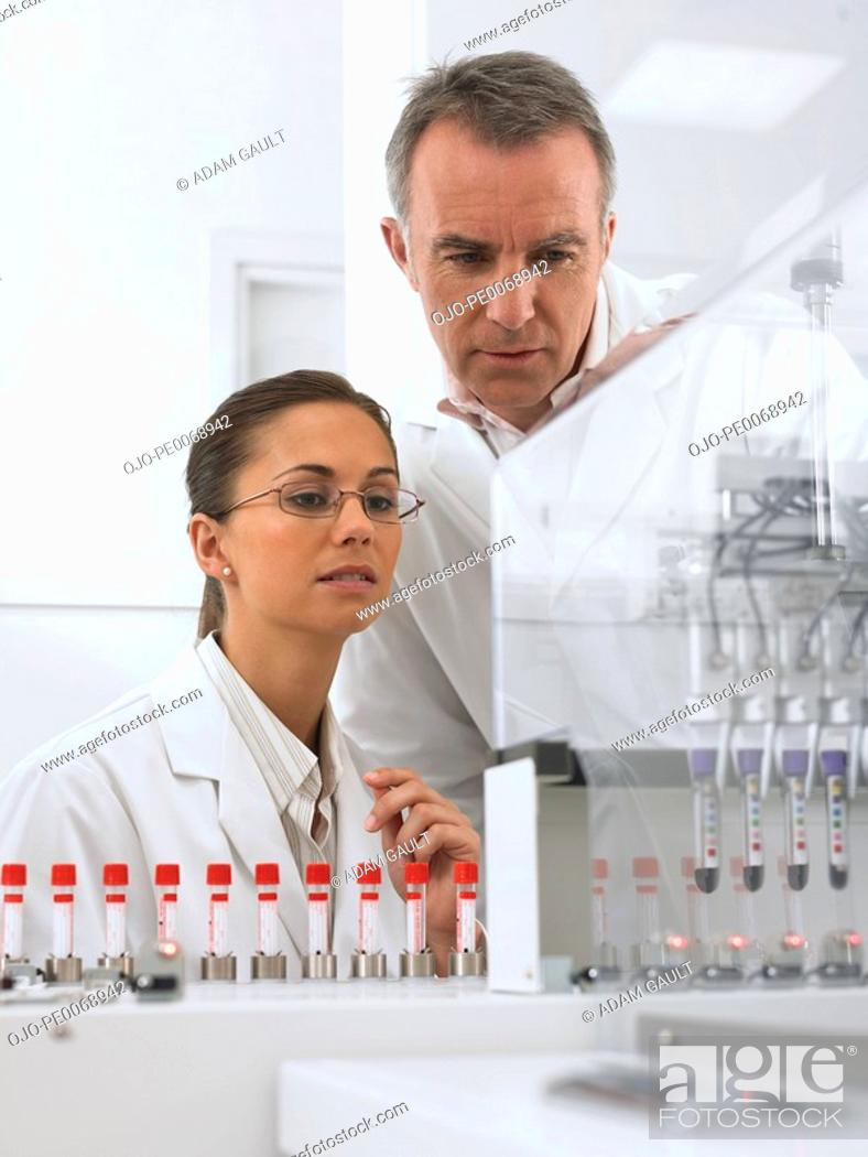 Stock Photo: Scientists watching test tubes in machine.