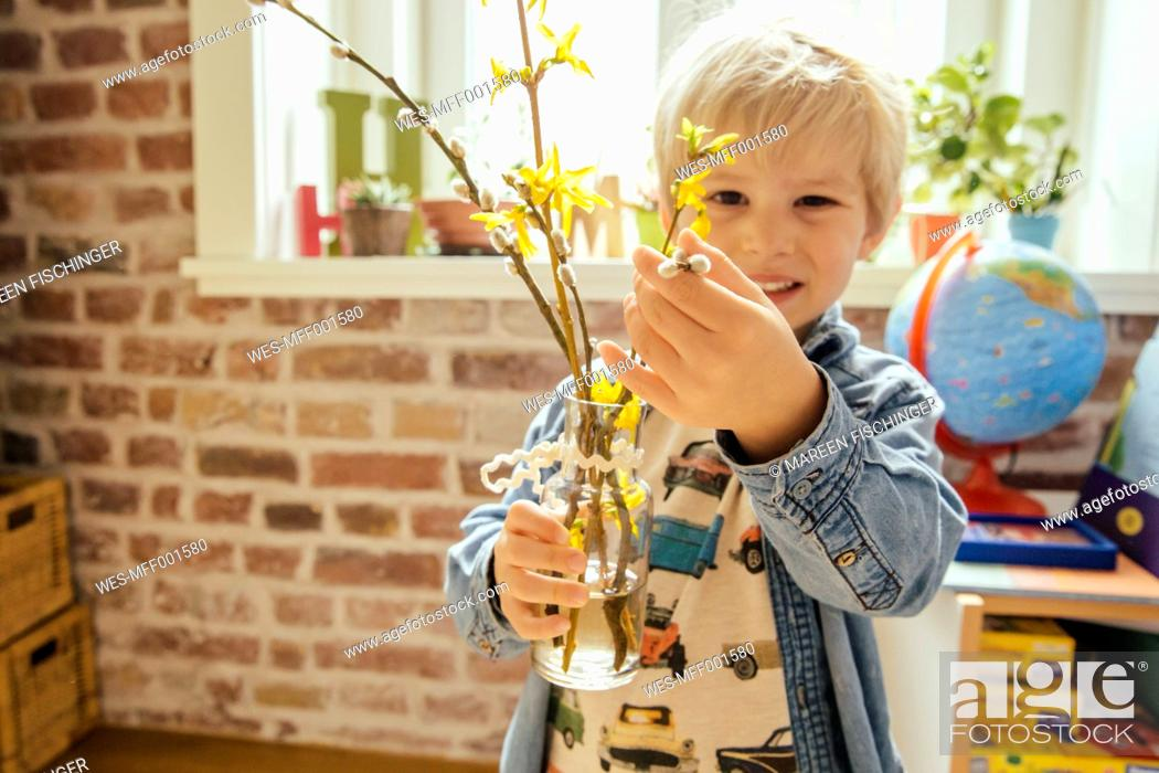 Stock Photo: Little boy holding vase with willow catkin and forsythia.