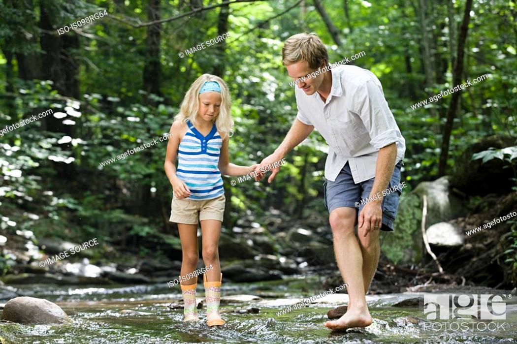 Stock Photo: Father and daughter in river.