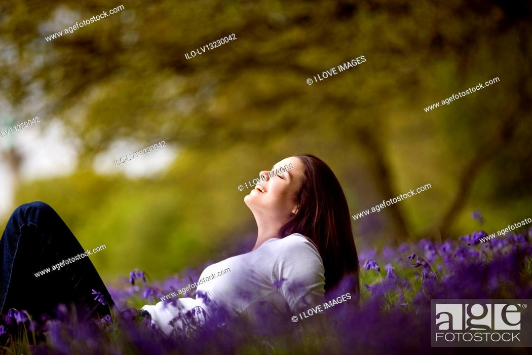Stock Photo: A young woman lying amongst bluebells.