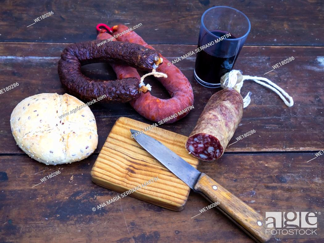 Stock Photo: Iberian pork sausages on an old wooden board with a wedge of sheep cheese, an antique knife and a glass of red spanish wine.