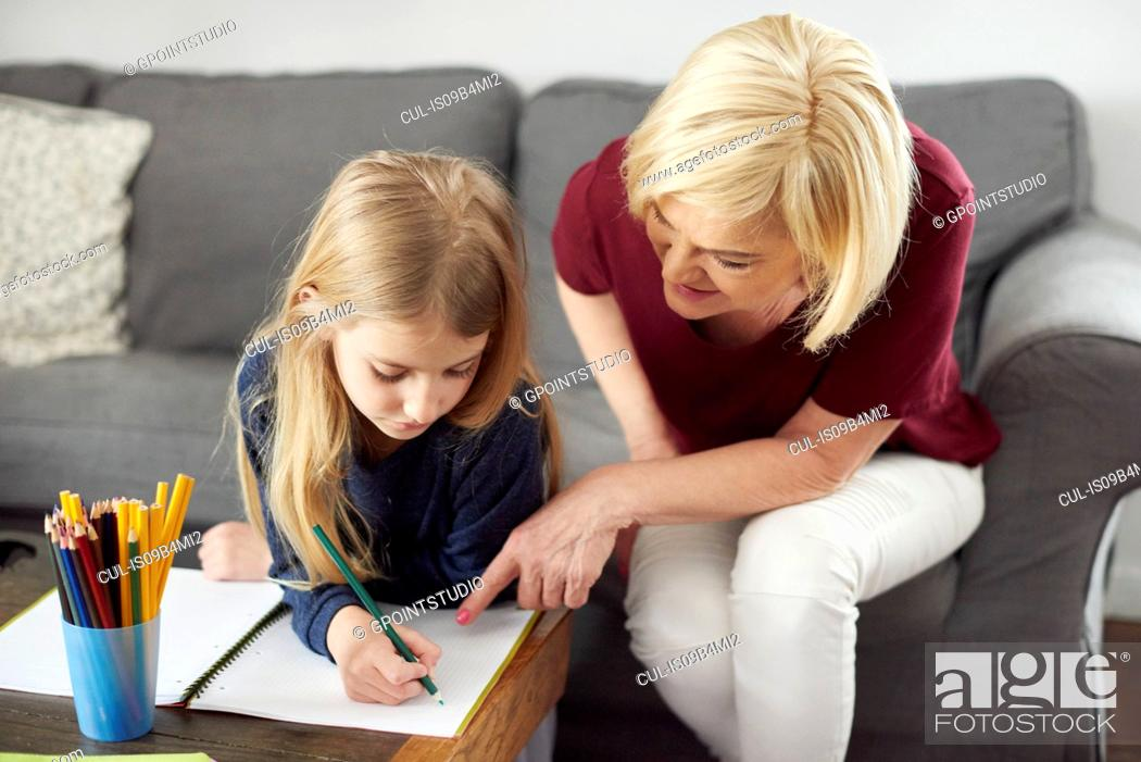 Stock Photo: Grandmother helping granddaughter with colouring at home.