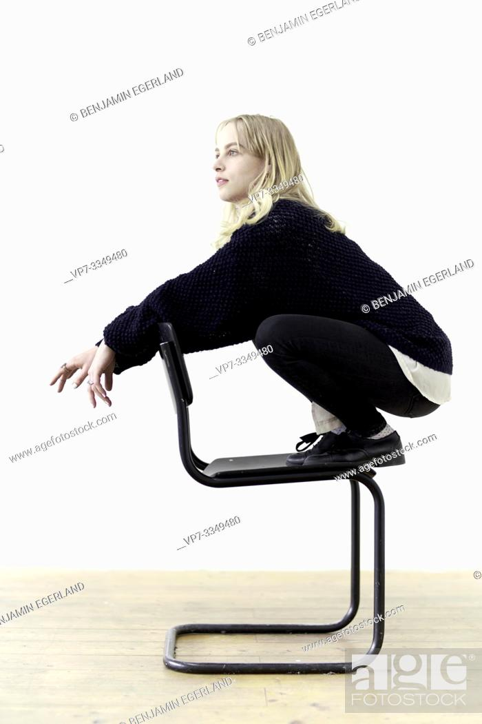 Stock Photo: young thoughtful woman on chair, contrarian.