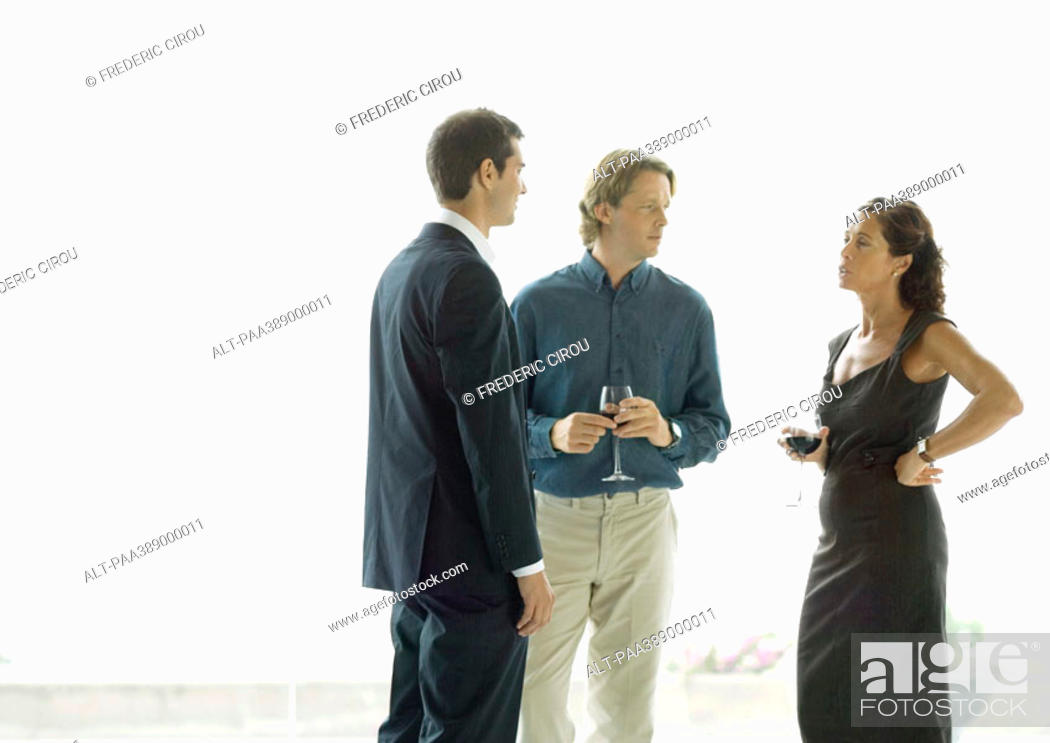 Stock Photo: Three adults standing with drinks, chatting.