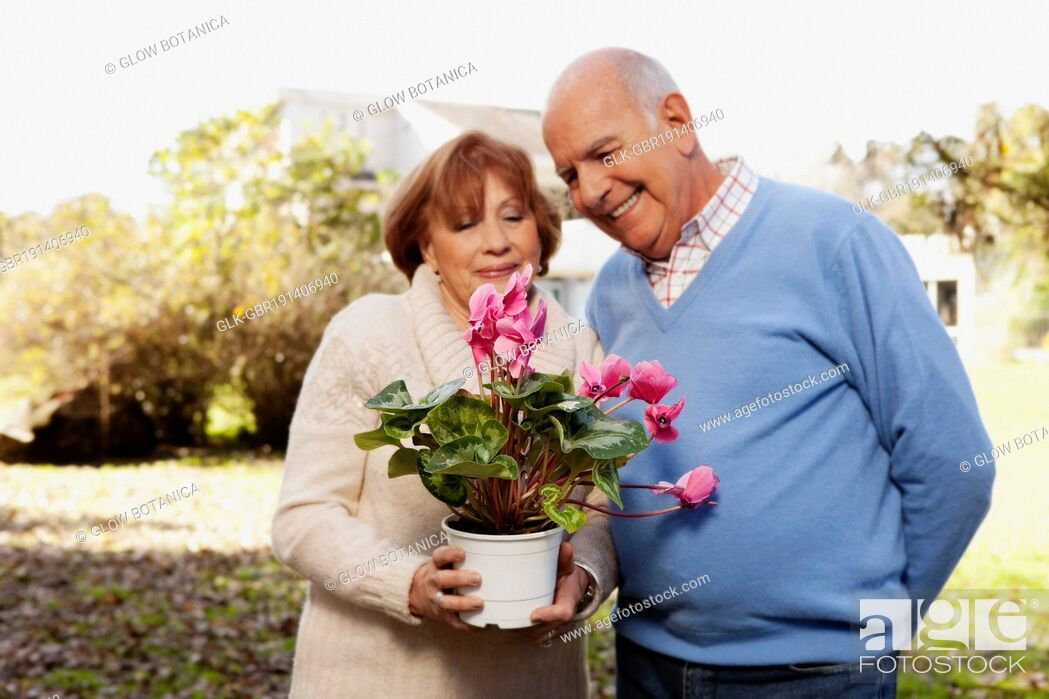 Stock Photo: Couple holding a potted plant in a park.