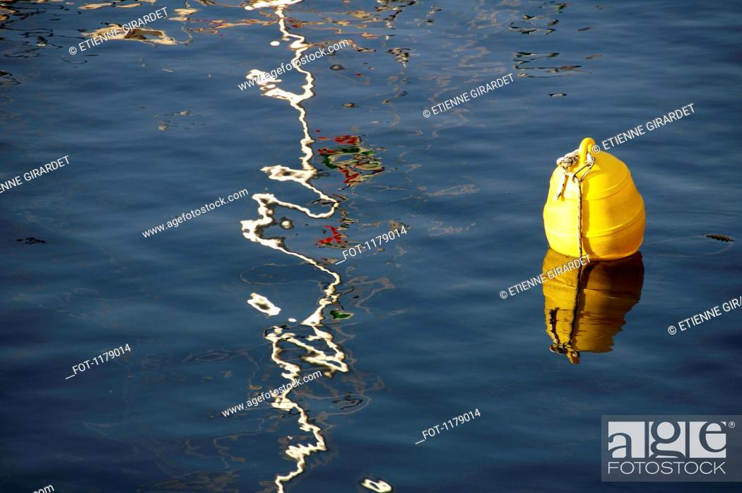 Stock Photo: A play of sunlight on water beside buoy.