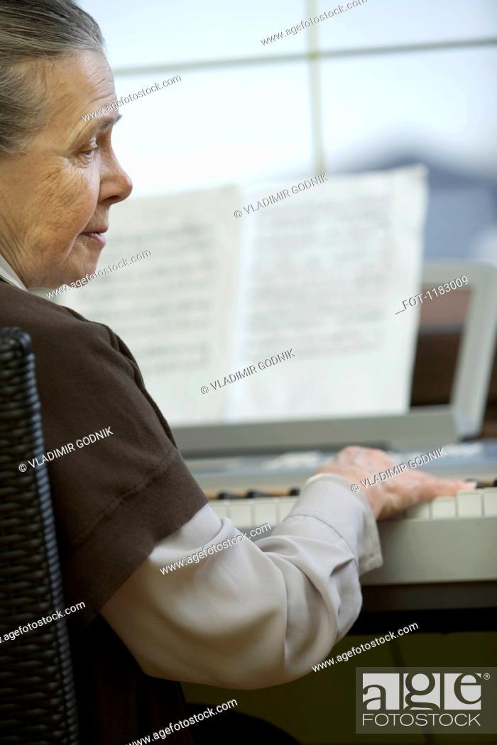 Stock Photo: A senior woman sitting at piano.