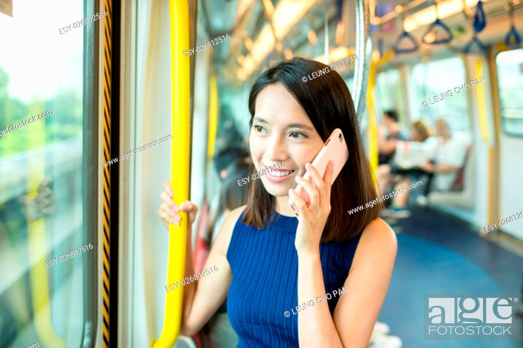 Stock Photo: Woman talk to cellphone inside MTR in Hong Kong.