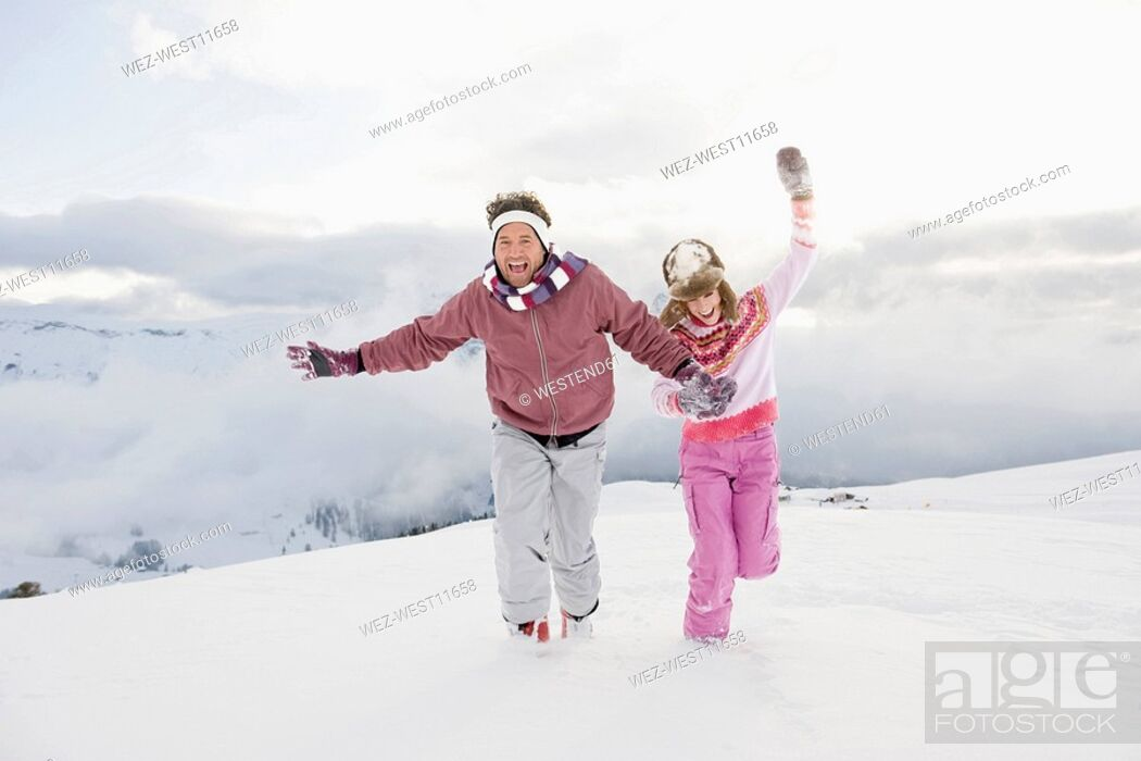Stock Photo: Italy, South Tyrol, Seiseralm, Couple running in snow, laughing.