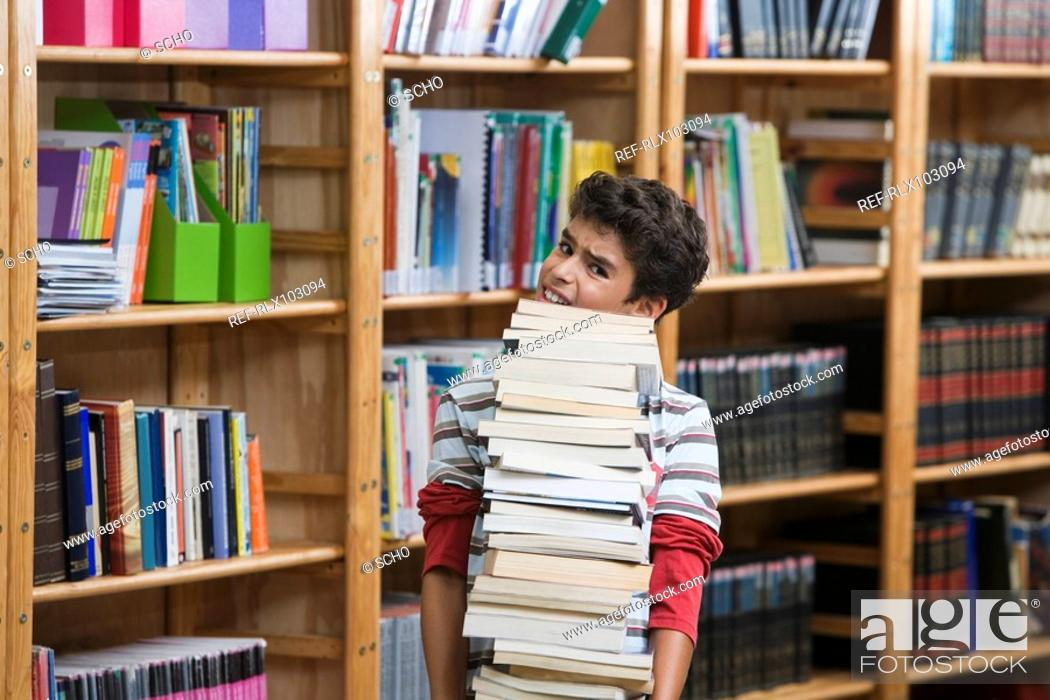Stock Photo: Boy 10-13 in library, straining to carry pile of school books.