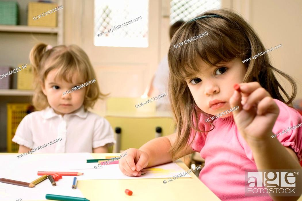 Stock Photo: Portrait of a girl showing a crayon with her friend sitting in the background.