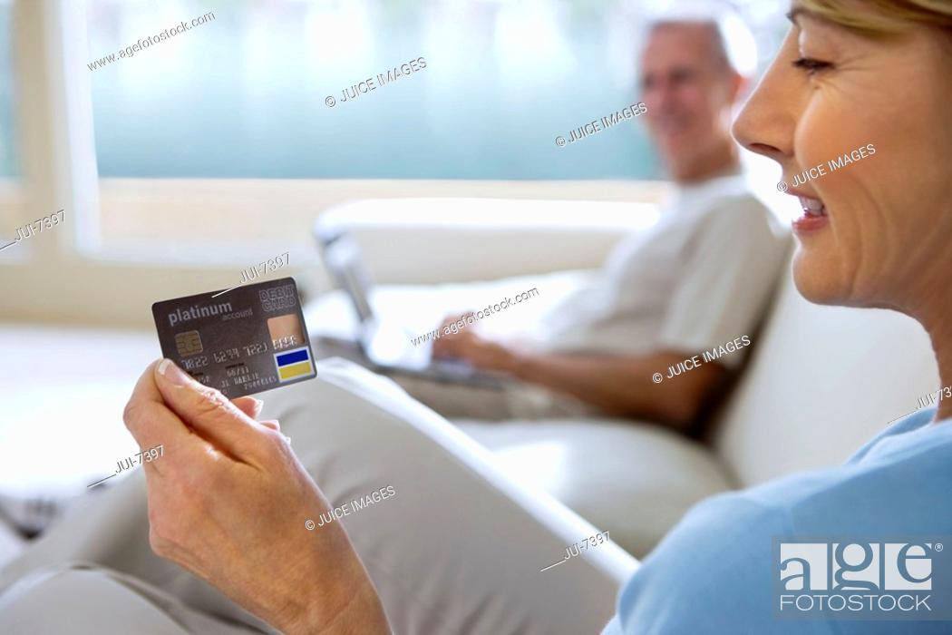 Stock Photo: Senior man sitting on sofa at home, using laptop, focus on mature woman holding credit card in foreground, smiling, side view.