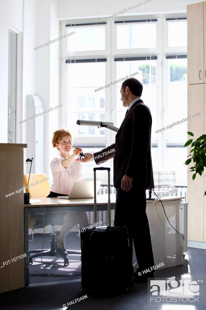 Stock Photo: A woman sitting at a desk handing a businessman keys.