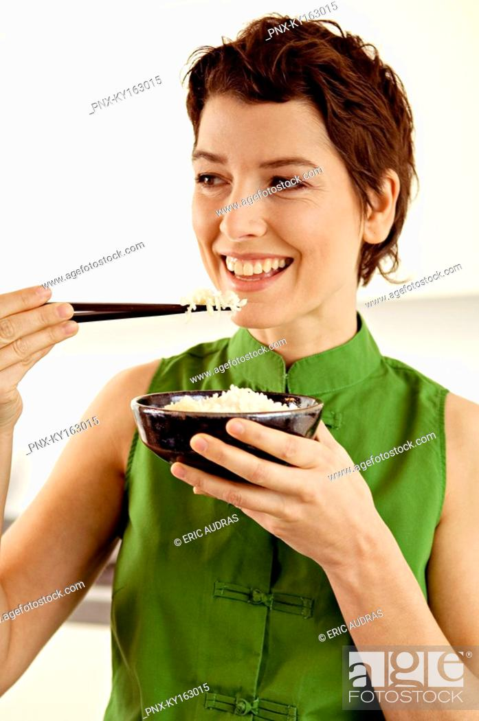Stock Photo: Close-up of a mid adult woman eating rice with chopsticks.