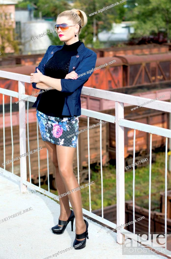 Stock Photo: the sexy woman on the bridge at a handrail, against cars, a subject beautiful women and railway roads.