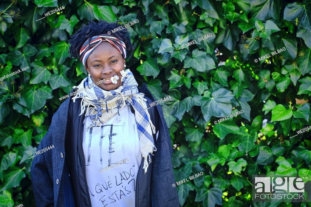 Imagen: Young african woman with an cool hair style and a t-shirt posing outdoor in a garden with a leaves background.