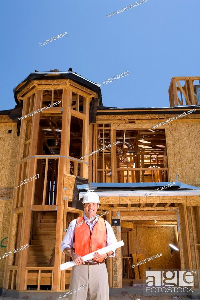 Stock Photo: Builder in hardhat on site, smiling, portrait, low angle view.