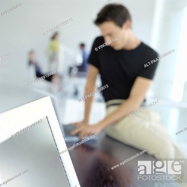 Stock Photo: Man sitting on edge of desk in office.