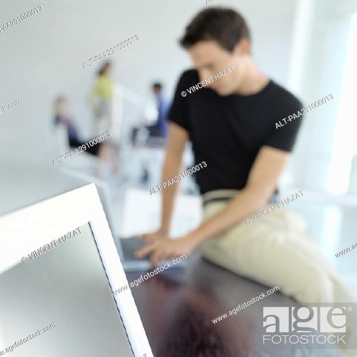 Stock Photo: Man sitting on edge of desk in office.