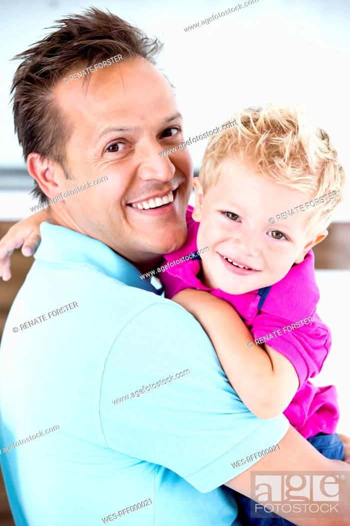 Stock Photo: Germany, Father carrying son, smiling.