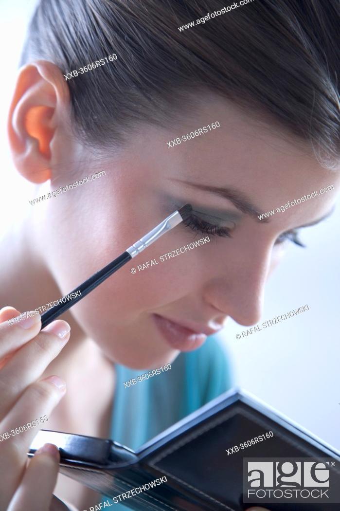 Stock Photo: woman putting eye shadow.