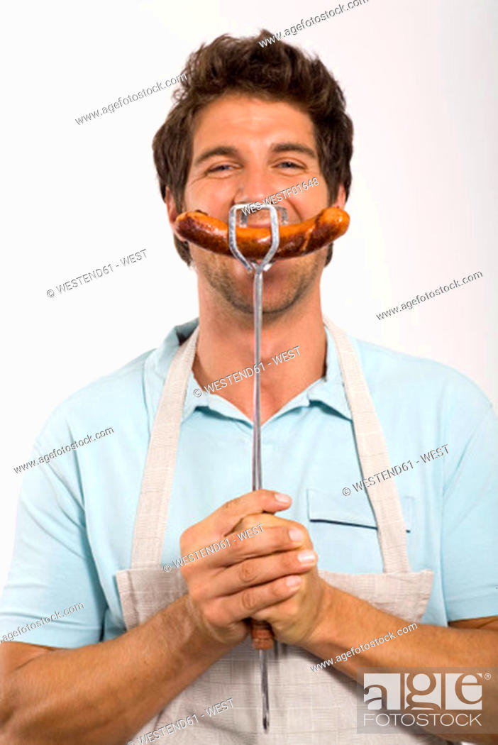 Stock Photo: Young man holding grilled sausage, close up, portrait.