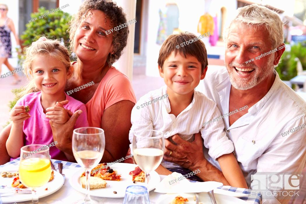 Stock Photo: Grandparents With Grandchildren Eating Meal At Restaurant.
