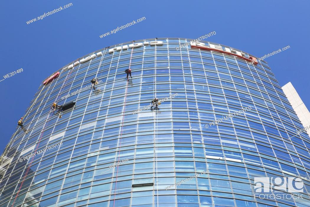 Stock Photo: Window washers hanging from ropes on outside of modern curved architectural glass and steel office tower, Tel Aviv, Israel.