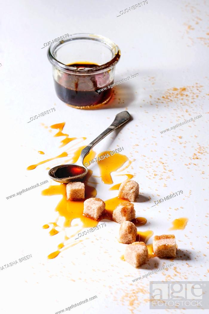 Stock Photo: Homemade liquid transparent brown sugar caramel in glass jar with spoon and cane sugar cubes over white marble background. Copy space.