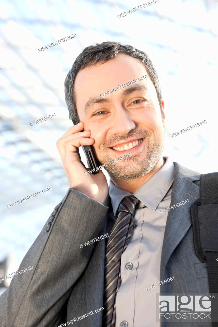 Stock Photo: Germany, Leipzig, Businessman using cell phone, smiling, portrait.
