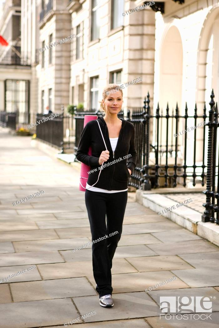 Stock Photo: A mid adult woman carrying a yoga mat, walking.