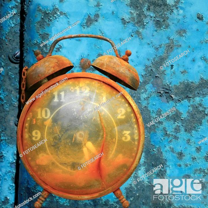 Stock Photo: Old weathered alarm clock against rusty blue metal background.