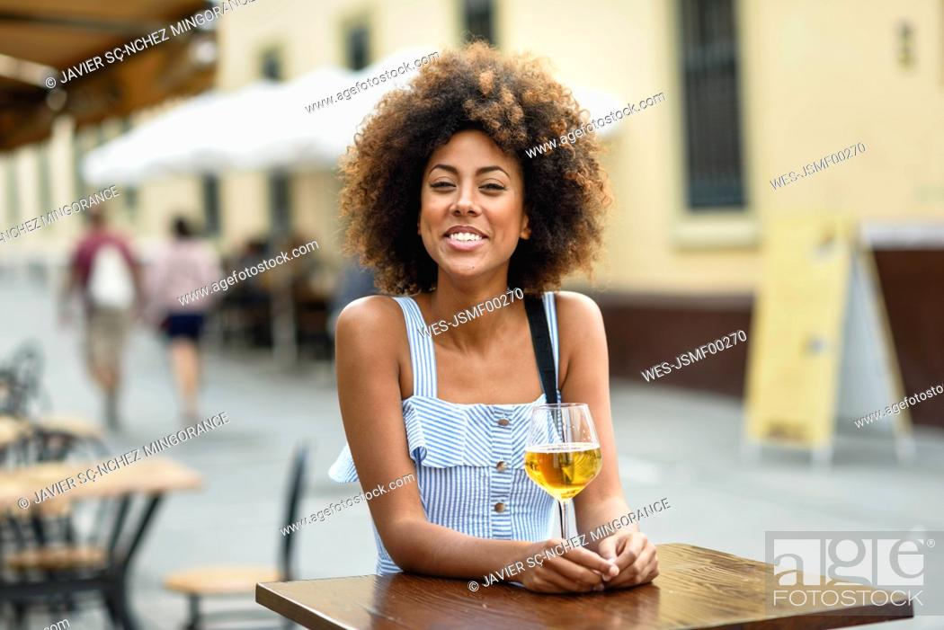Stock Photo: Portrait of happy young woman drinking beer outdoors.