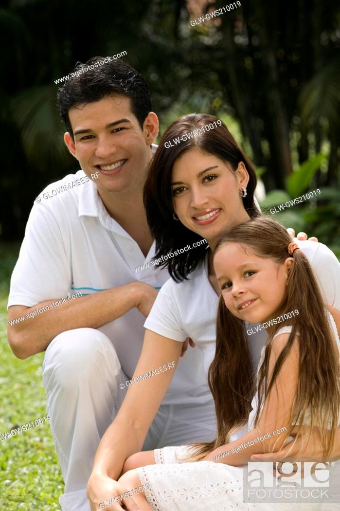 Stock Photo: Portrait of a young couple with their daughter in a park.
