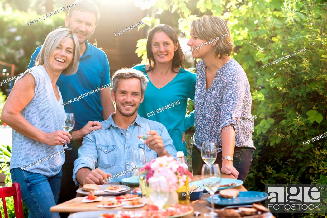 Stock Photo: Group of friends gathered around a table in a garden on a summer evening to share a meal. They are posing for a photo.