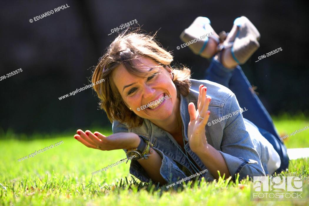 Stock Photo: Portrait of woman in a park smiling.