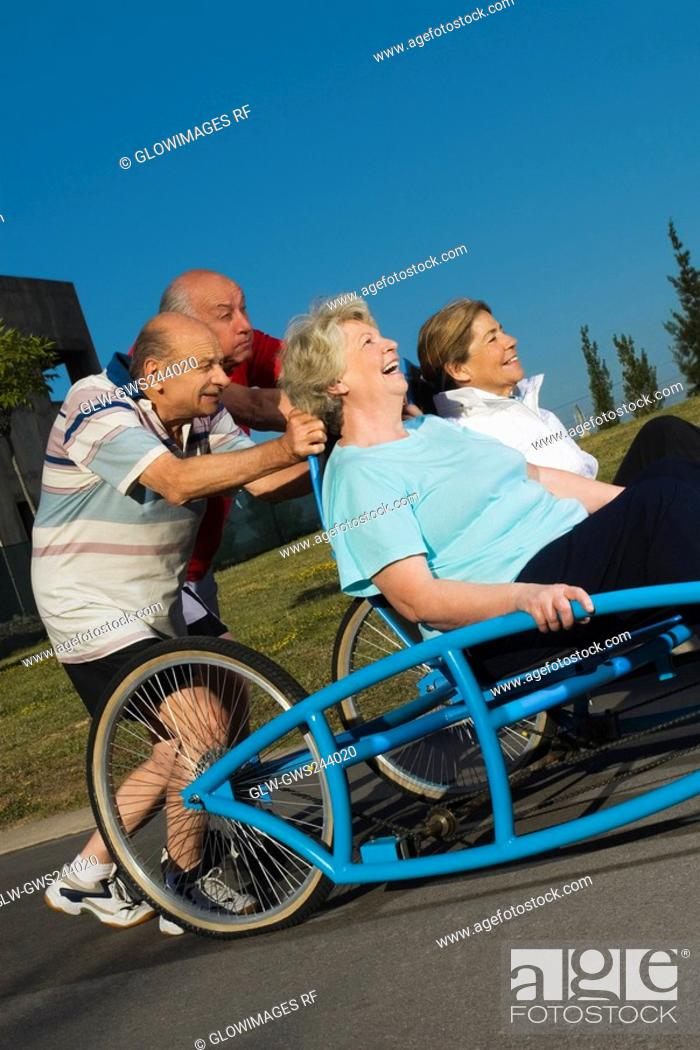 Stock Photo: Two senior women sitting on a quadracycle and two senior men pushing it.