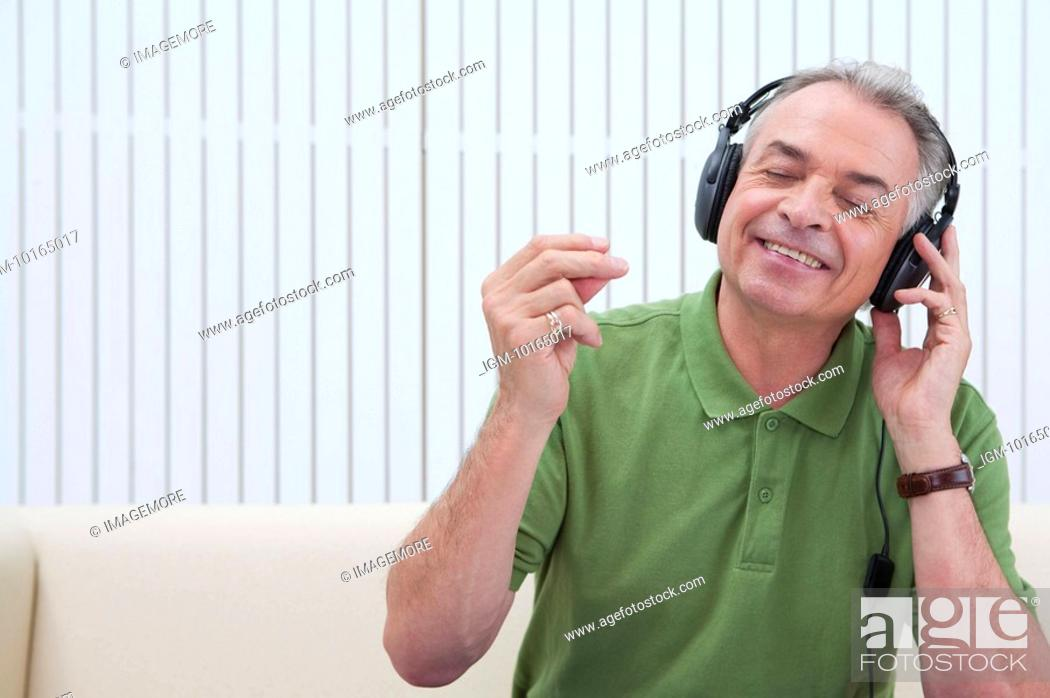 Stock Photo: Domestic Life, a senior man listening to music with eyes closed and smiling.