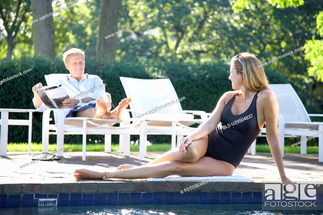 Stock Photo: Woman lying by pool, man reading on lounge chair.