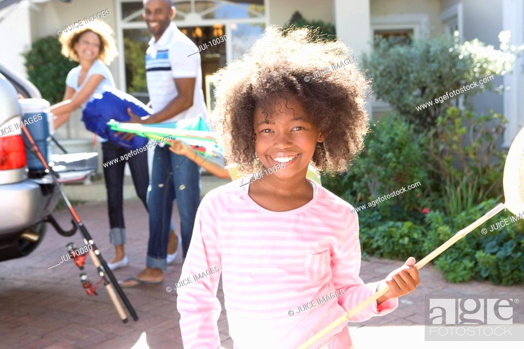 Stock Photo: Girl 8-10 with fishing net in driveway, parents in background, smiling, portrait.