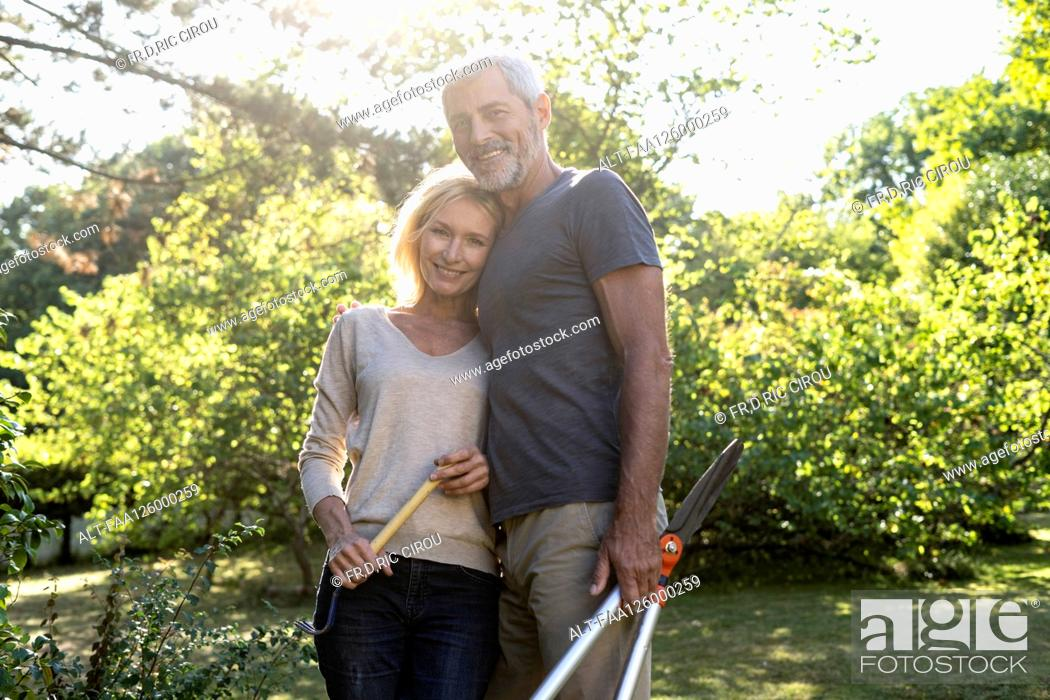 Stock Photo: Portrait of mature couple standing in backyard.