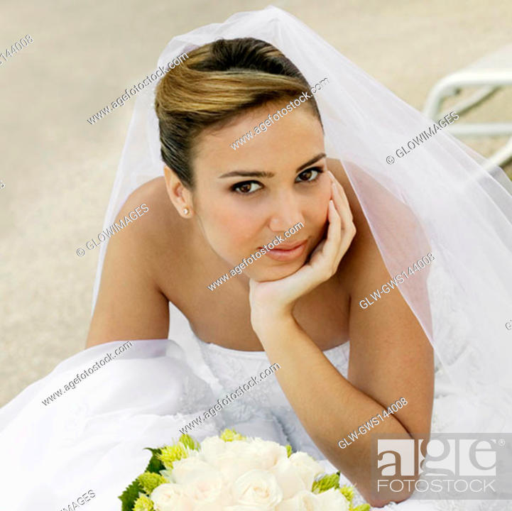 Stock Photo: Portrait of a bride sitting with her hand on her chin.