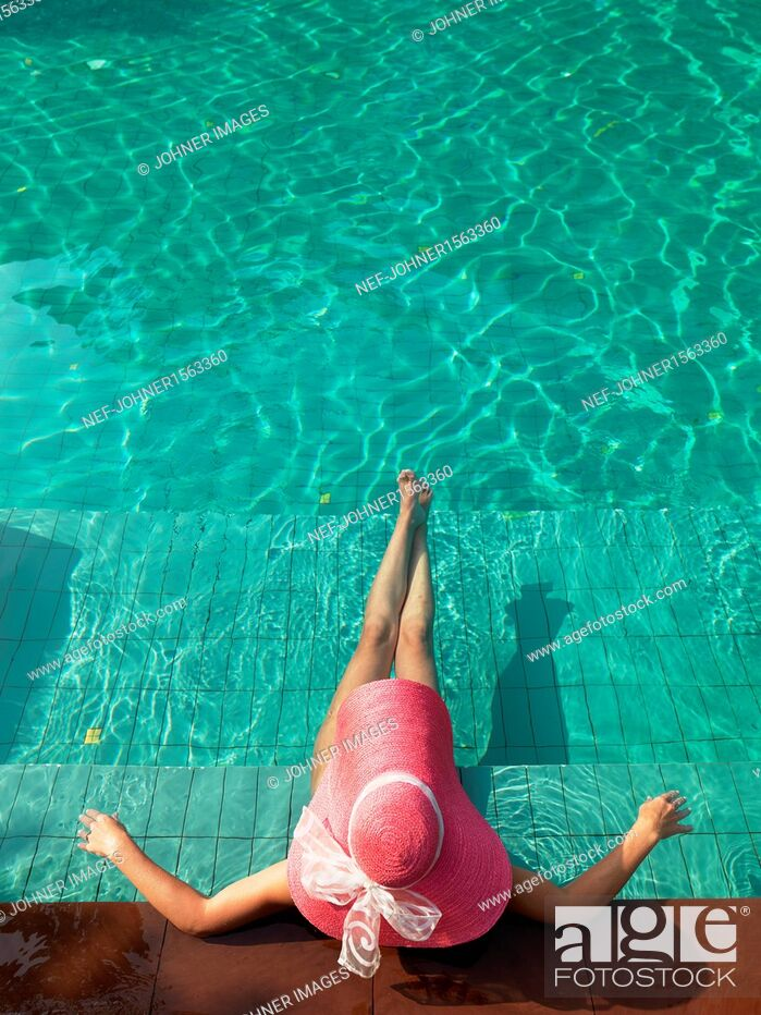Stock Photo: Woman resting at edge of swimming pool.