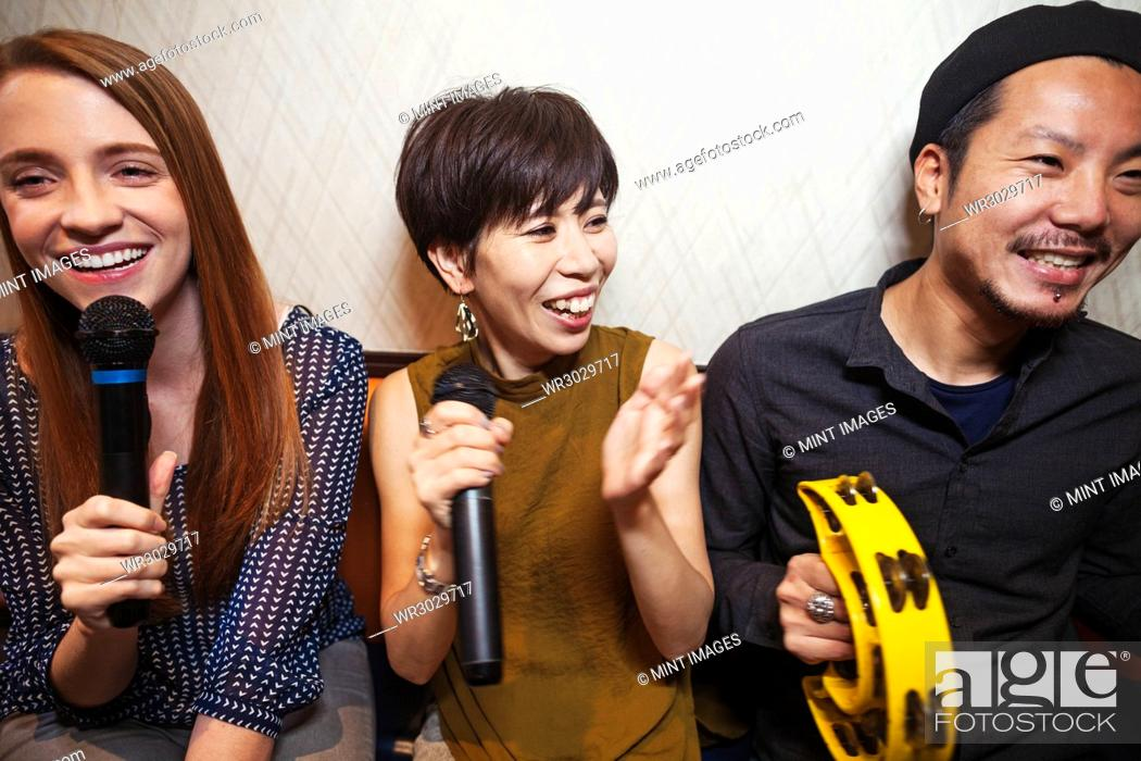 Stock Photo: Three people, two women and man, holding microphone, singing, making music.