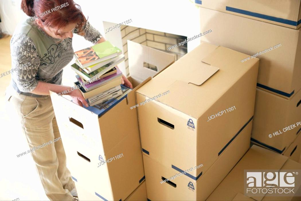 Stock Photo: Woman packing books.