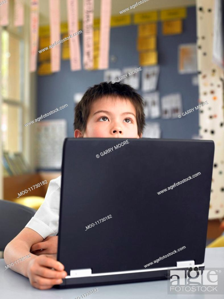 Stock Photo: Elementary schoolboy sitting behind opened laptop in classroom.