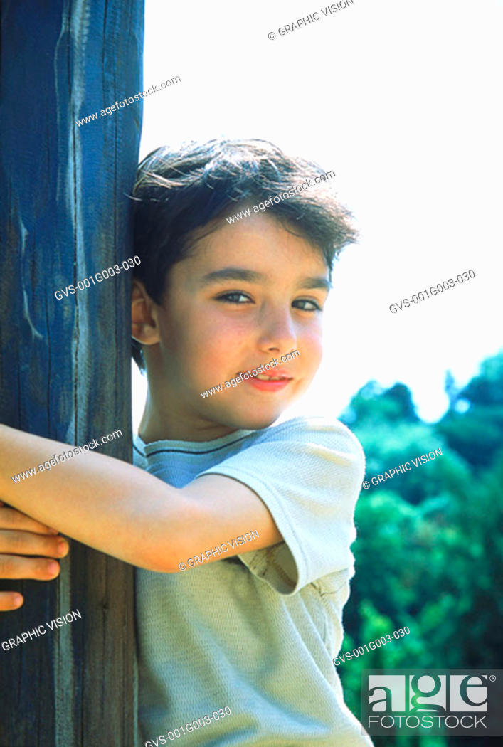 Stock Photo: Young boy smiling hugging a wooden post.