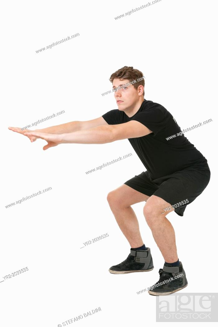 Stock Photo: Young man squatting on a white background.