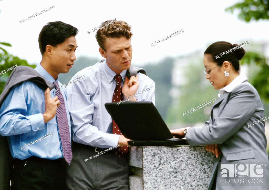 Stock Photo: Two men and a woman looking at laptop computer.