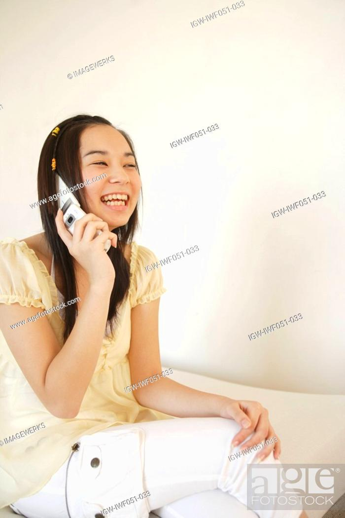 Stock Photo: Teenage girl 14-15 using mobile phone, smiling.